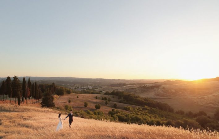 newlyweds walk in the yellow fields of the tuscan countryside at sunset
