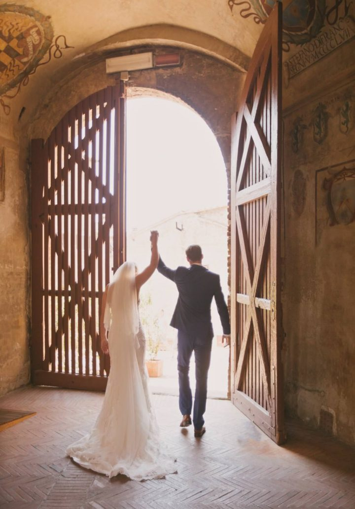 bride and groom walk for the first time as husband and wife through a gate in certaldo