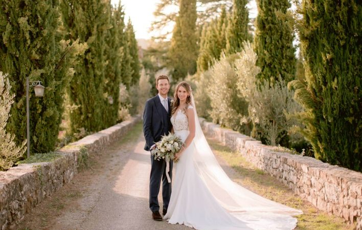 bride and groom posing in the dirt roads of Tuscany