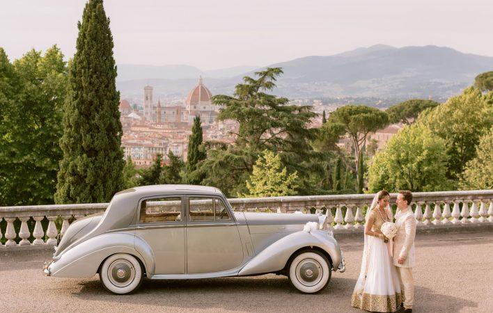 newlyweds posing with the bentley