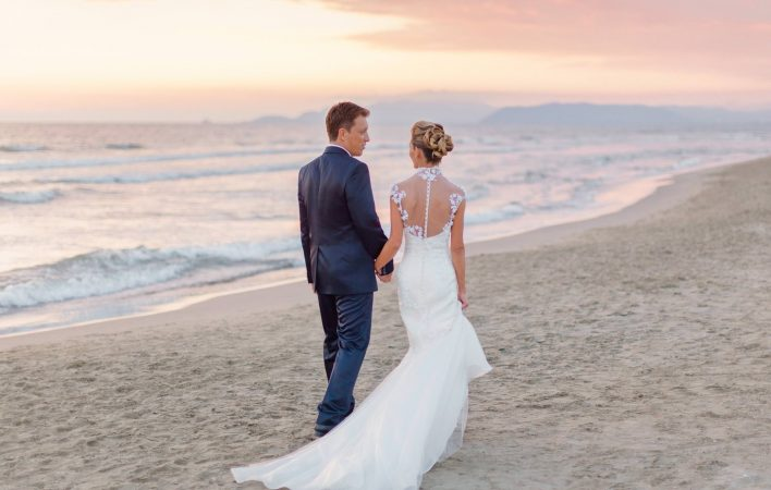 bride and groom strolling on the beach of bagno annetta at sunset