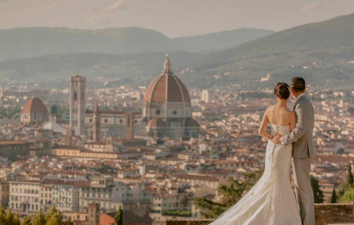 newlyweds watching the dome of florence at sunset from piazzale michelangelo