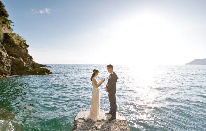 couple exchanging vows on a pier with the view of the ocean