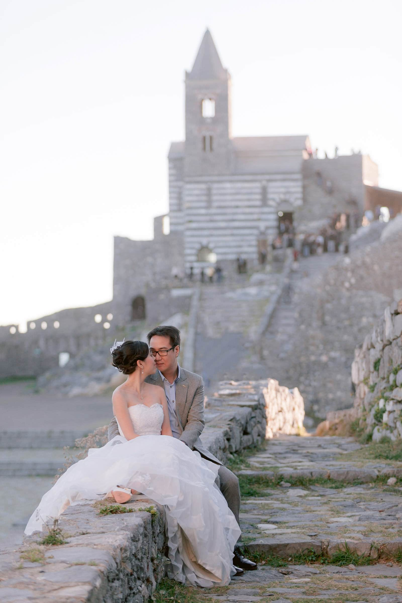 bride and groom with San Pietro church as a backdrop